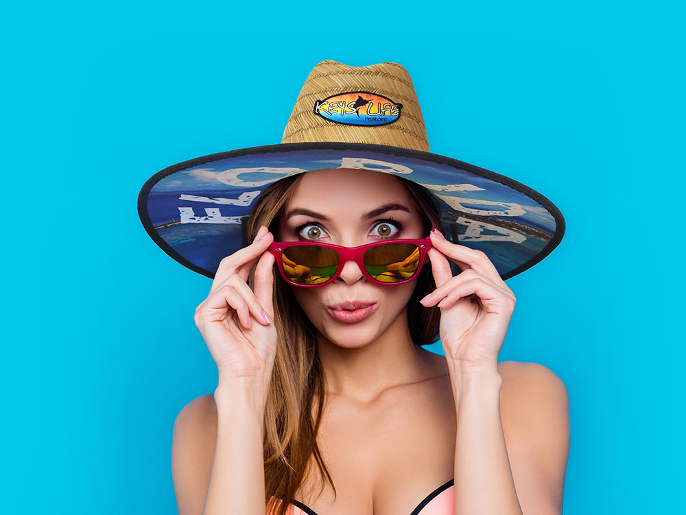 Woman wearing a Keys Life Restore lifeguard hat